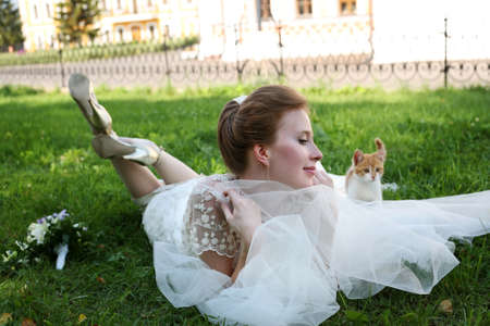 getting married: Beautiful bride and kitten in park