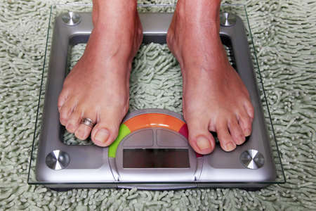 foot girl: Bathroom scales isolated against green carpet