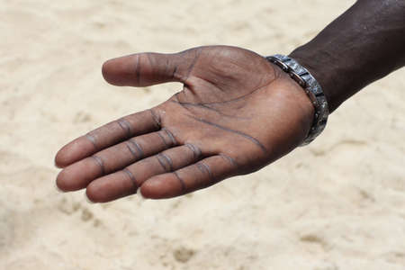 male palm:  Open hand of the black man on a background of sand Stock Photo