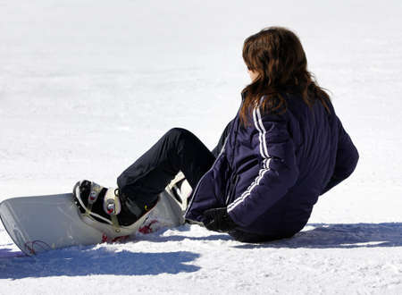 congenial: Young woman with snowboard sitting in the snow Stock Photo