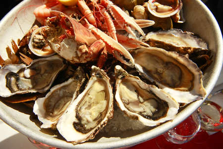 shucked: A platter of fresh raw oysters on ice at an outdoor cafe  Stock Photo