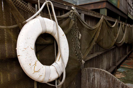 Old net and old lifebuoy are hanging on land photo