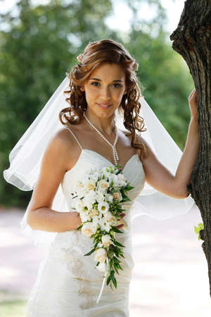 contestant: The beautiful bride with bouquet in park