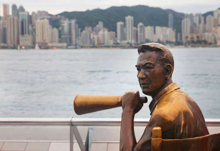 HONG KONG - APRIL 26: Statue and skyline in Avenue of Stars on April 26, 2014 in Hong Kong, China. The promenade honours celebrities of the Hong Kong film industry as the famous city attraction. Stock Photo - 27852475