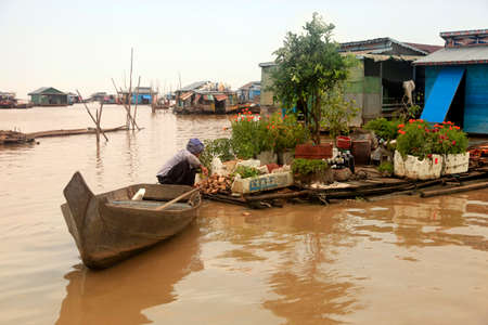 stilt house: SIEM REAP, CAMBODIA - APRIL 06, 2014: An unidentified woman on a floating village on Tonle Sap lake in Siem Reap, Cambodia on April 06, 2014.