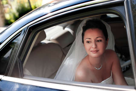 getting ready: The beautiful bride with bouquet in car Stock Photo