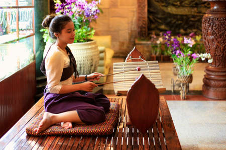 gamelan: PHNOM PENH, CAMBIDIA - APRIL 6, 2014: Unidentified local girl plays in traditional gamelan instruments outside hotel on April 06, 2014 in Phnom Penh, Cambodia.  Editorial