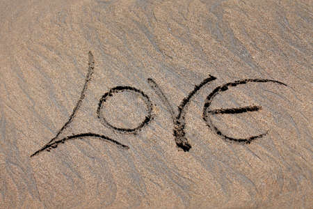 The word love is written by someone on sand photo