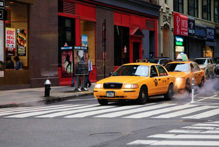recognised: New York, United States - May 19, 2013: Yellow New York Taxicab driving through Manhattan. The yellow taxi has become a recognised icon of the city