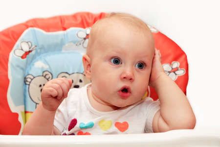 baby on chair: Surprised little girl sitting in baby chair Stock Photo