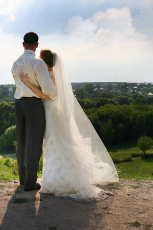 Beautiful the bride and groom on landscape background photo