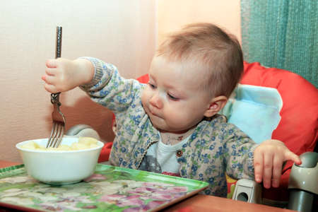 nurseling: Little girl with fork in hand Stock Photo