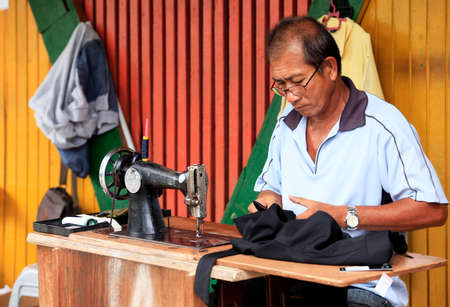 malaysia culture: Kota Kinabalu, Malaysia-  December 31, 2014: Street tailor with his old mechanic sewing machine at work in his small shop. This kind of job is very common in Malaysia.