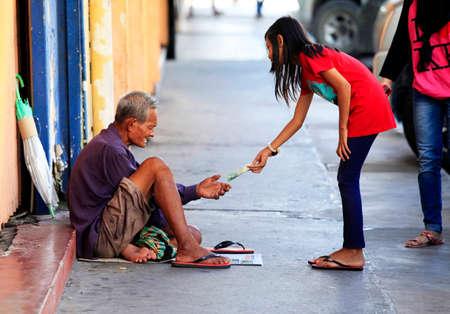 gives: Kota Kinabalu, Malaysia - January 3, 2015: Young girl gives money to a beggar on the street Kota Kinabalu in Borneo, Malaysia Editorial