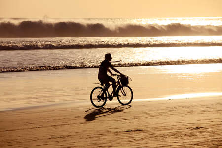 Woman on a bicycles goes on seacoast. Bali, Indonesia photo