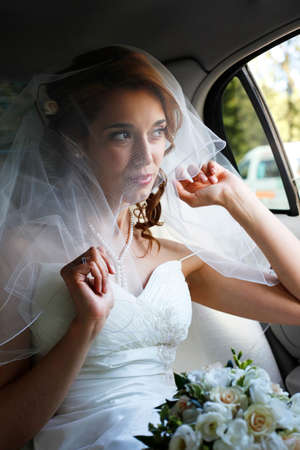 Beautiful bride with wedding bouquet in white car photo