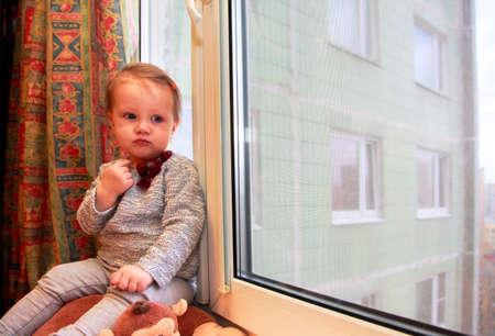 windowsill: Sad little girl on a windowsill at home