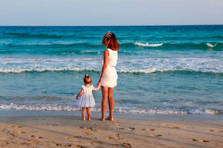 aucasian: Happy mother holding her daughter on the beach