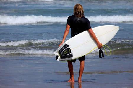 granola: Surfista sobre una costa esperando la gran ola. Bali  Foto de archivo