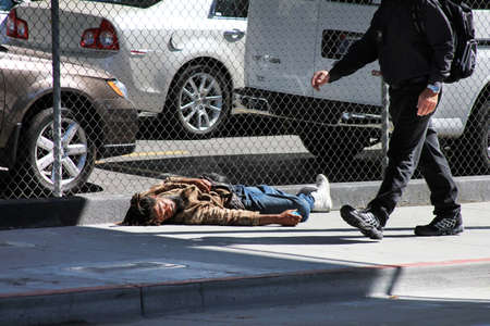 homeless man: Los Angeles, CA, USA - September 23, 2011: Homeless man sleeps on the street near the fence in the center of Los Angeles