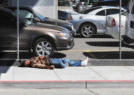 wino: Los Angeles, CA, USA - September 23, 2011: Homeless man sleeps on the street near the fence in the center of Los Angeles