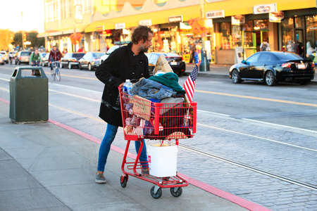 ca he: San Francisco, CA, USA - September 24, 2013: Homeless Man with Shopping Cart on the streets in San Francisco. He carries all of his belongings with him in a shopping cart