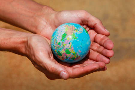 mundo manos: Male hands with the small globe on a background of sand