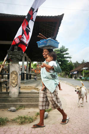 disadvantaged: Ubud, Indonesia - October 30, 2007: The Indonesian woman with a small daughter in balines to a village on Bali Editorial