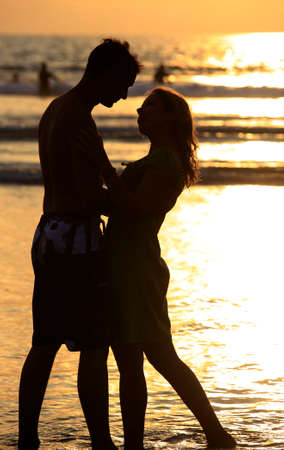 young lady: Silhouette to the in love pair on a sunset