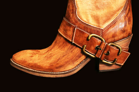 western attire: Female boot of the cowboy on a black background