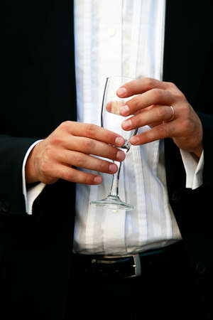 suit  cuff: Glass of champagne in a hand of the groom