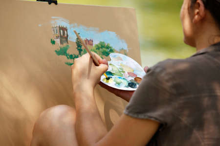A young girl paints a picture in the park photo