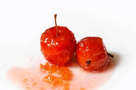 jarabe: Manzanas rojas en jarabe de rosas con pequeños trozos de calabacín sobre fondo blanco aislado