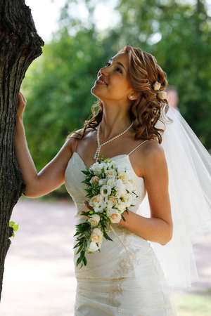 The beautiful bride with bouquet in park photo