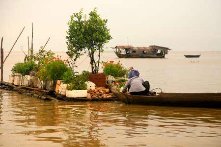 tonle sap: SIEM REAP, CAMBODIA - APRIL 06, 2014: An unidentified woman on a floating village on Tonle Sap lake in Siem Reap, Cambodia on April 06, 2014.