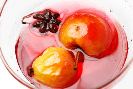 rosaceae: Red apple in rose syrup with anise over isolated white background