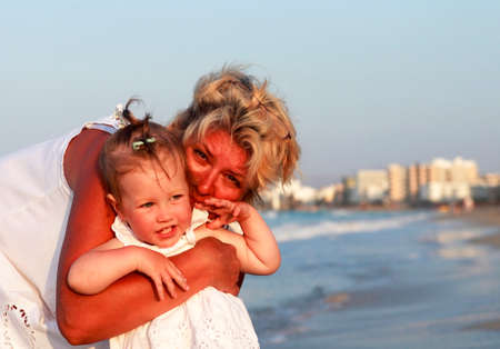 Grandmother with a little granddaughter on the beach photo