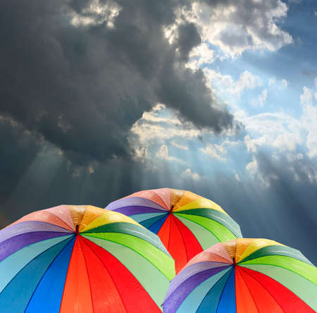 rain weather: Rainbow umbrella against blue sky