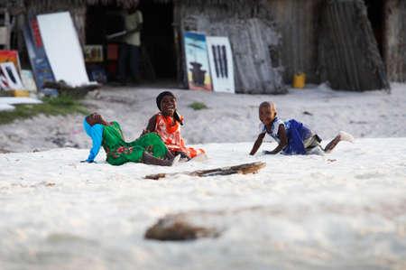 Zanzíbar, Tanzania - 9 de enero 2016: Tres niñas africanos juegan en la playa y que ríe en Zanzíbar