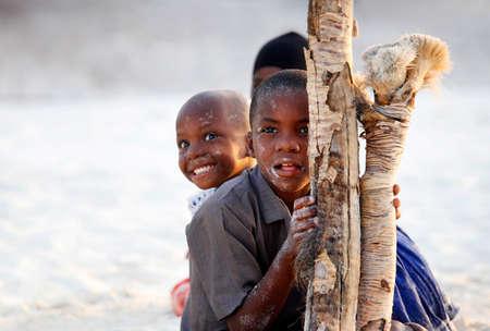 Sansibar, Tansania - 9. Januar 2016: Drei afrikanische Kinder Versteck spielen und am Strand auf Sansibar