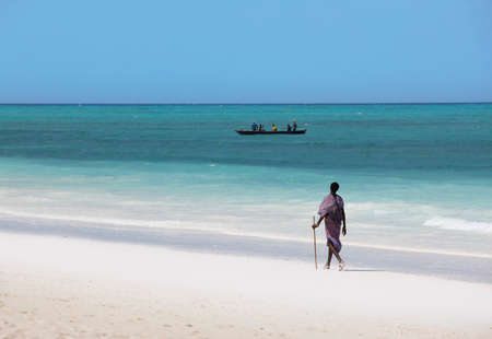 fishman: Zanzibar, Tanzania - January 6, 2016: Young massai man with colorful traditional clothes, headdress and self made shoes walking through the water on the Nungwi beach.