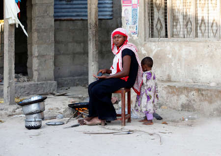 african descent: Zanzibar, Tanzania - January 9, 2016: African Muslim woman to cooks near his house, her child is playing nearby. Traditional situation for Zanzibar