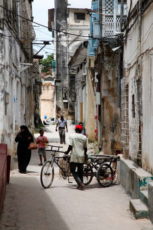 Stone town, Tanzania - December 30, 2015: Stone Town. Woman in Zanzibar all have to wear black burka when they go outside, even girls have to wear scalf on their heads. It is a Muslim life stile. Streets of the town are always lively.