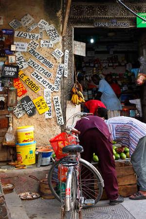 persona viajando: ciudad de piedra, Tanzania - 30 de diciembre de, 2015: la ciudad de piedra. Calles de la ciudad son siempre animado. Hay muchas tiendas, restaurantes y bares, donde los turistas pueden relajarse y comprar suvenirs. He aquí un hombre al parecer, la recogida de las placas de matrícula de edad.