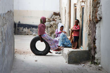 black lady: Zanzibar, Tanzania - January 1, 2016: African Muslim women holding baby her arms and her children on the street of Stone Town in Zanzibar
