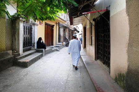 old street: Stone Town, Zanzibar, Tanzania - January 1, 2016: Adult man in traditional clothes in Zanzibar alleyway Editorial