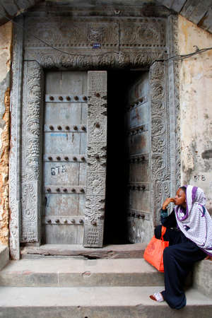 old town house: Stone Town, Tanzania - January 1, 2016: Traditional house with old door and woman in traditional Muslim clothes sitting on the street of Stone Town. Editorial