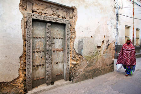 old town house: Stone Town, Tanzania - January 1, 2016: Woman in traditional Muslim clothes walking on the street of Stone Town. On her left side there is traditional house with old door and in background is another house.