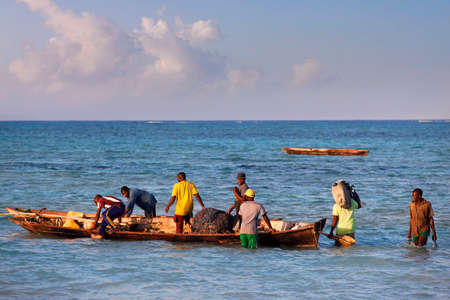 fishman: Stone Town Zanzibar, Tanzania - January 6, 2016: A dhow traditional sailboat in the background and a crowded fishing boat and fishman in the foreground in the Indian Ocean just off the island of Zanzibar, Nungwi