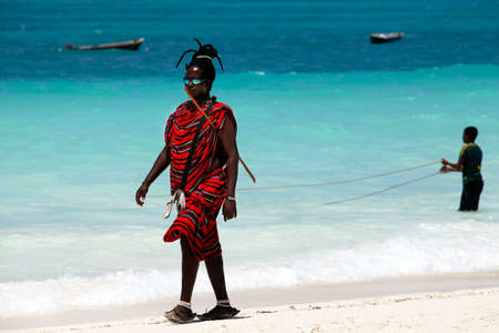 handcarves: Zanzibar, Tanzania - January 6, 2016: Young massai man with colorful traditional clothes, headdress and self made shoes walking through the water on the Nungwi beach.